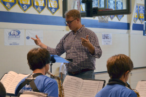 Music teacher Brad Light conducts the high school band during the pep assembly.