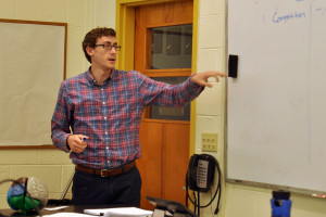 Science teacher Stephen Shannon explains the day's lesson while his students take notes.