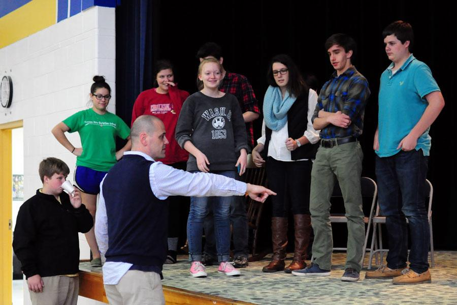 Director Miller shows seniors Kayley Forshey, Hayden McBee, Madeleine McCully, and freshman Nora Dooley and Patrick Lague where to walk on the stage.