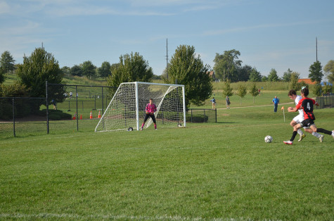Defending the goal, senior Bryce Johnston looks on as sophomore Josh Kucera steals the ball from an opponent.