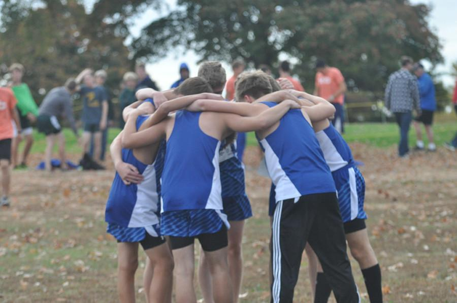 Cross country boys huddle up before the race to get pumped up.