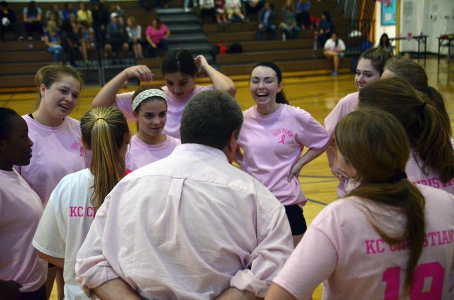 The volleyball takes a breather during their Pink Night match and talks with head coach Terry Littleton.