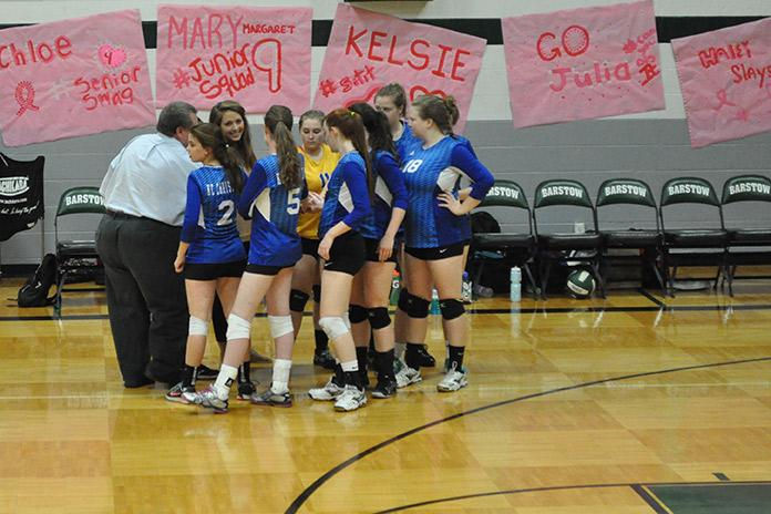Volleyball team huddles together to pray before the match.
