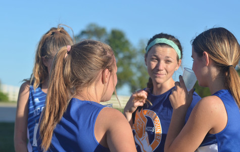 After their race, the girls cross country team talks with assistant coach Lily Young. Young ran for KCC herself four years ago.