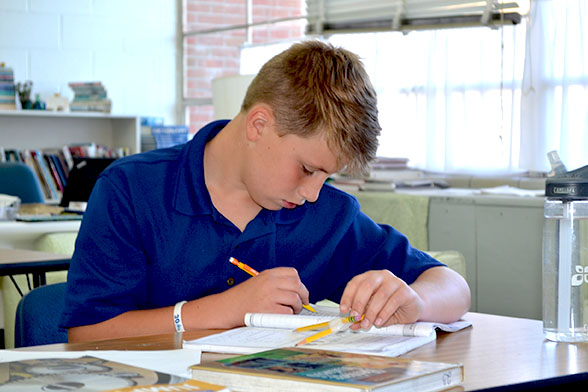 Working on an assignment during study hall, sixth grader Luke White looks at his paper.