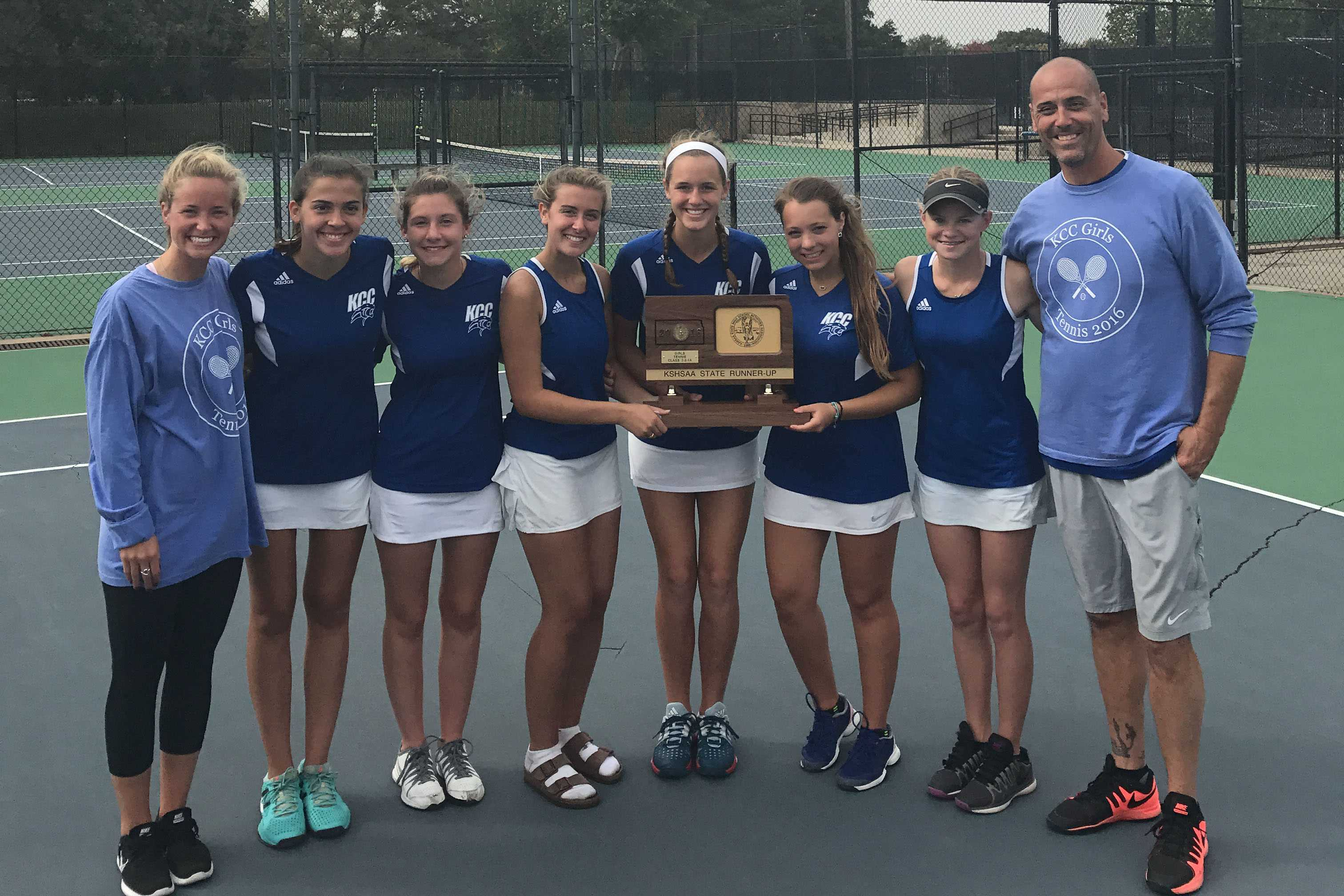 The tennis team holds their second place state plaque.
