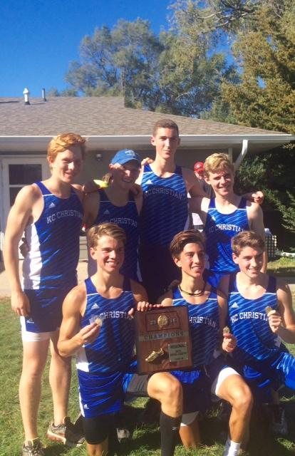 Boys varsity cross country team show off their plaque for their first place finish at Regionals.