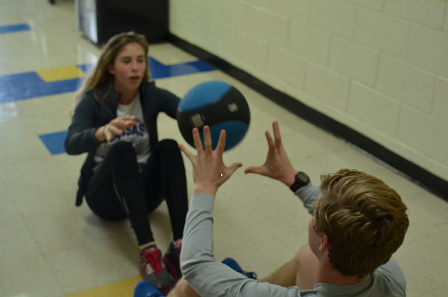 Seniors Maya Mastin and Joel Connealy pass a medicine ball back and forth to train.
